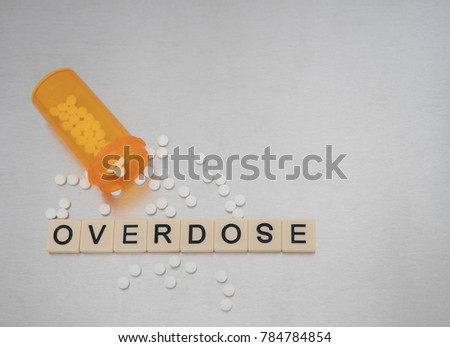 Overdose spelled with tile letters placed in a row with an open bottle of oxycodone tablets. Photographed from above on a stainless steel background. Image has copy space.