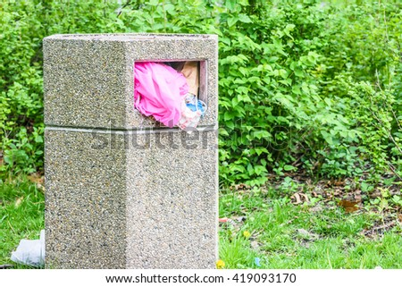 Overfilled trash of large bin for rubbish at park - stock photo