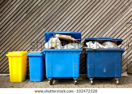 overfilled trash of large wheelie bins for rubbish, recycling and garden waste - stock photo