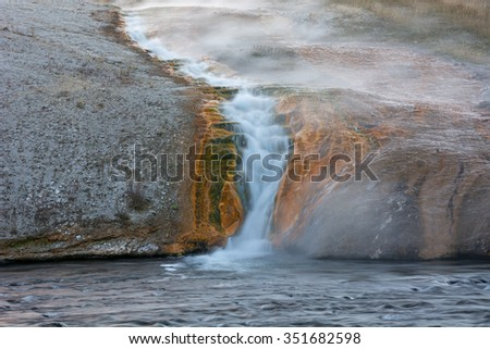Overflow cascade from the Excelsior Geyser Crater in the Midway Geyser Basin of Yellowstone National Park, Wyoming. - stock photo