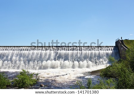 Overflow of water on the man-made storage pond. View from down point - stock photo