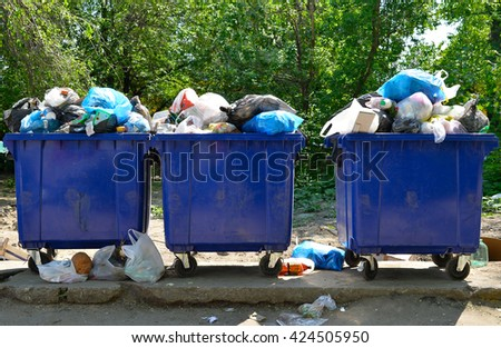 Overflowing garbage bins with household waste in the city - stock photo