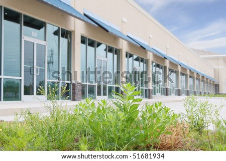 Overgrown parking lot of office building - stock photo