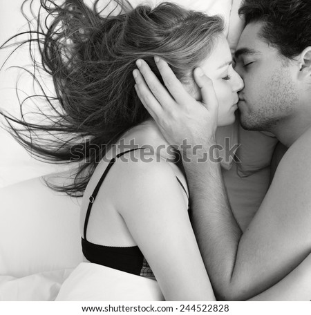 Overhead black and white portrait of a young couple caressing laying in bed together being romantic hugging and kissing. Couple in a relationship having sex in a white bed, home interior lifestyle. - stock photo