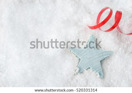 Overhead Christmas background shot.  A pale blue wooden star, resting in white artificial snow, with red swirl of ribbon above and copy space to the left.