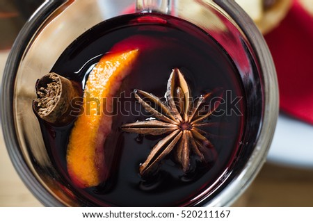 Overhead close up (macro) shot of a glass of mulled wine with star anise, orange and cinnamon stick.  Red napkin and mince pie in soft focus background.