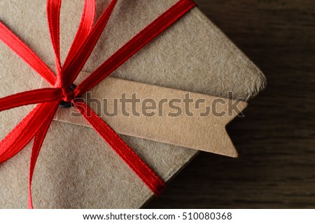 Overhead close up of a blank label tied to a plain brown  gift box with red ribbon on oak wood surface.