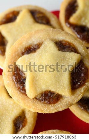 Overhead close up of a stack of Christmas mince pies with star shaped pastry toppers and filling exposed.  Red napkin and white plate below.