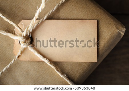 Overhead close up of aged and weathered old style blank parcel tag, tied with string to a package wrapped in brown paper.