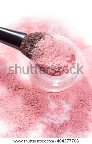 Overhead close up of one open jar of spilled pink blush powder with thick tipped brush on a white background
