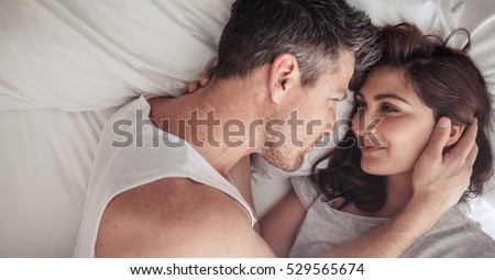 Overhead Close Up Of Young Couple Lying In Bed Together Romantic Love Looking