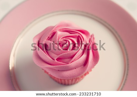 Overhead detail of vintage style pink rose frosted cupcake - stock photo
