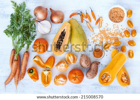 Overhead horizontal of fresh orange toned vegetables and fruit raw produce on white rustic background, pumpkin butternut carrot papaya pawpaw capsicum pepper sweet potato cherry tomatoes chilli orange - stock photo