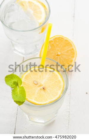 overhead making glass with cold drink and lemon, white wood