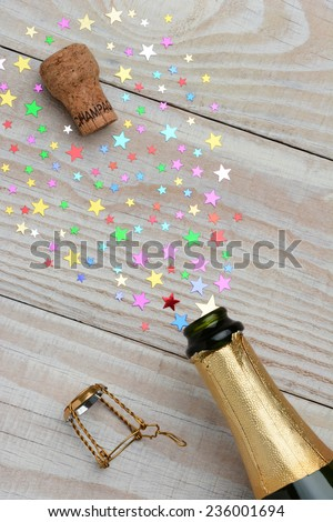 Overhead of a bottle of champagne with the cork popping on a rustic wood table. The spray from the bottle is made of colorful stars. With copy space it is perfect for New Years party and celebrations - stock photo