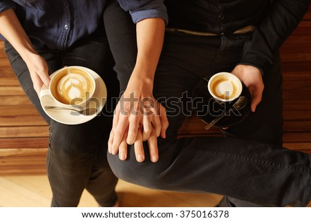 Overhead of a couple sitting close with coffee - stock photo