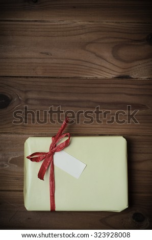 Overhead of a gift package wrapped in pale yellow and tied to bow with red raffia ribbon on wood planked surface.  Hues adjusted and vignette added for retro or vintage style effect. - stock photo