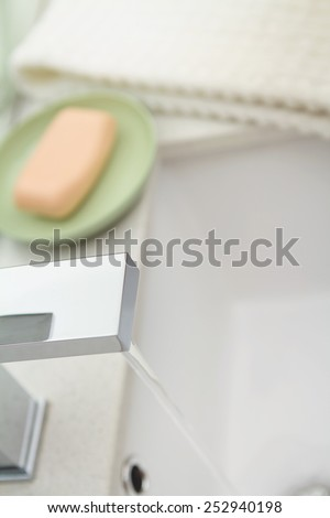 Overhead of a running water modern bathroom tap - stock photo