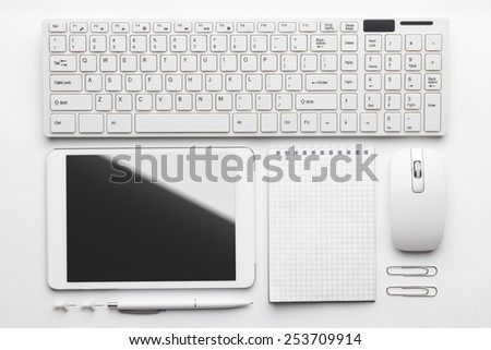 overhead of essential office objects in order on white desk. notebook, computer keyboard and mouse, tablet pc, pen, push pins, paper clips  - stock photo