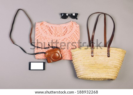 Overhead of essentials modern girl. / Summer outfit of hipster woman on grey background. - stock photo