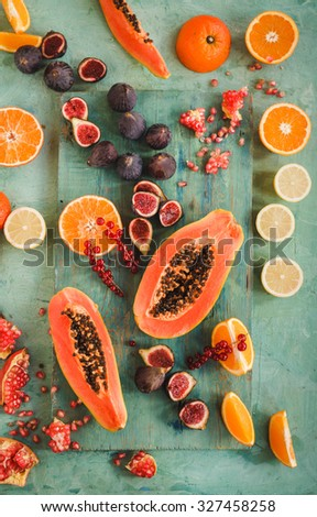 Overhead of fresh various fruits raw produce on rustic blue background, papaya, orange, lemon, figs, pomegranate, red berries. Rustic colorful image from above on a green background. - stock photo