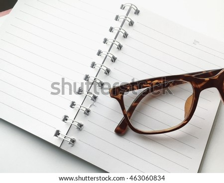 Overhead of open notebook with glasses on a desk In the style of vintage filter. Close-up.
