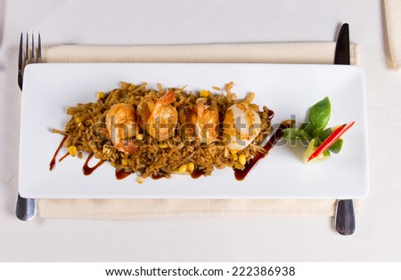 Overhead of Seafood Fried Rice with Shrimp and Scallops on Square Plate at Restaurant Place Setting - stock photo