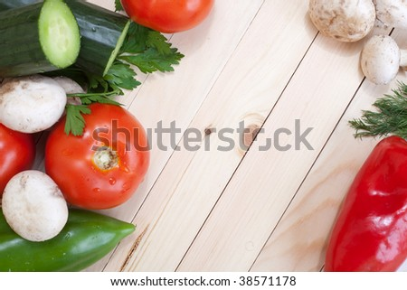 Overhead of table top with fresh veggies around the corners with empty space for text - stock photo