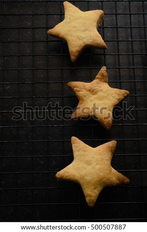 Overhead of three star shaped Christmas biscuits (cookies) on top of black wire cooling rack, on right side of frame.