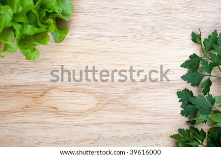 Overhead of wooden breadboard with some fresh lettuce and parsley leafs - stock photo