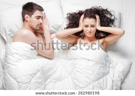 Overhead of young couple in the bed. Snore. Attractive woman is angy with her sleeping boyfriend holding hands on head. - stock photo