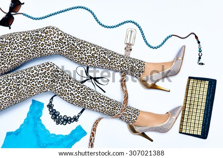 Overhead Outfit. Fashion stylish clothes set. Woman sexy legs. Essentials party accessories. Glamor necklace, sunglasses. Trendy leggings, heels, creative look. Unusual modern.  Top view, background - stock photo