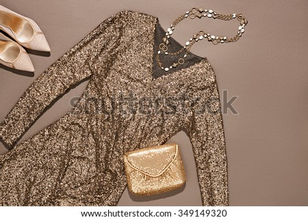 Overhead outfit Top view. Fashion clothes set, sequins dress and accessories. Glamor creative, trendy gold clutch, necklaces, earrings, luxury shoes heels.  Unusual elegant evening party essentials - stock photo
