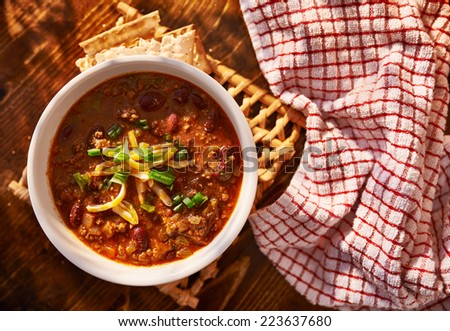 overhead photo of a bowl of chili with cheese and green onions - stock photo