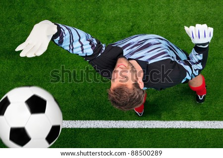 Overhead photo of a football goalkeeper missing saving the ball as it crosses over the line. Slight motion blur on the ball, focus is on his face. - stock photo