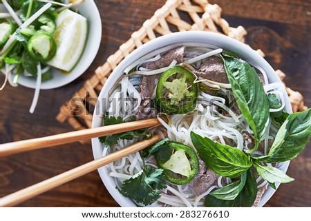 overhead photo of eating vietnamese beef pho - stock photo