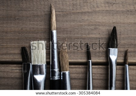 Overhead photograph of a variety of artist's paintbrushes arranged on old, faded wood. - stock photo