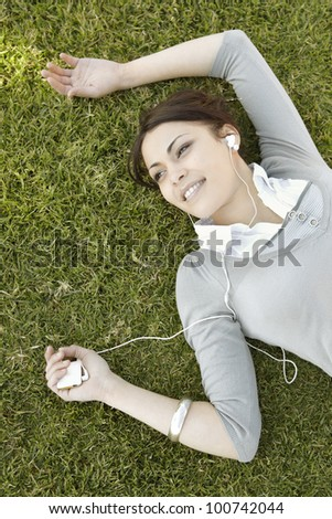 Overhead portrait of a young woman listening to music on her headphones while laying down on green grass. - stock photo