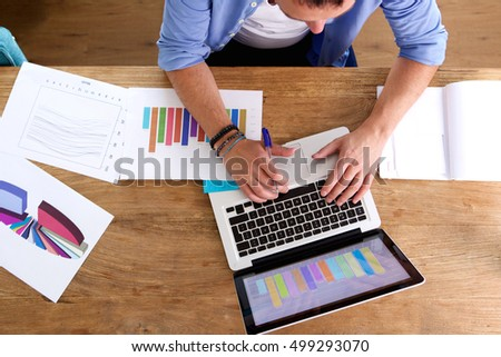 Overhead portrait of man working at his desk on laptop and charts