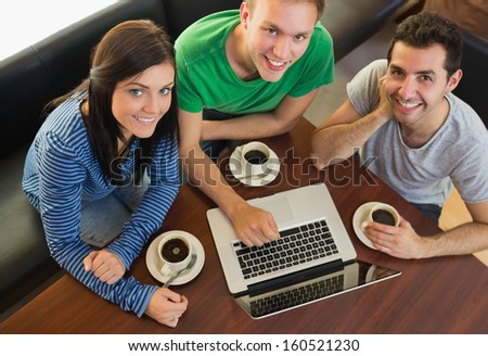 Overhead portrait of three students using laptop while having coffee at  the coffee shop - stock photo