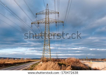 Overhead power line in front of cloudy sky - stock photo