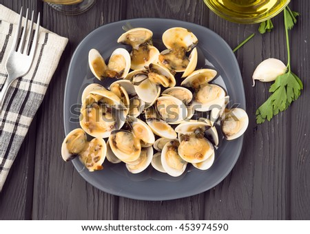 overhead shoot full of clams in sauce dish over black wood gray - stock photo