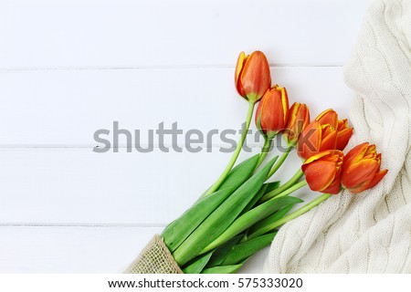 Overhead shot a bouquet of orange and yellow tulips wrapped in toile and burlap fabric and a cozy knit throw blanket over white wood table top. Flat lay top view style.