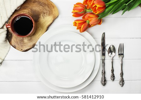 Overhead shot an empty dinner plate with coffee and a bouquet of springtime tulips over a white wood table top. Flat lay top view style.