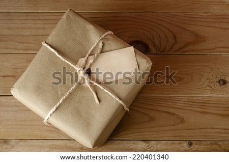 Overhead shot of a brown paper parcel, tied with string.  Blank label faces upwards to provide copy space.  Set on an old, worn wooden table. - stock photo
