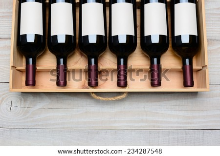 Overhead shot of a case of red wine bottles with blank labels  on a rustic white wood table with copy space at the bottom. Horizontal format. - stock photo