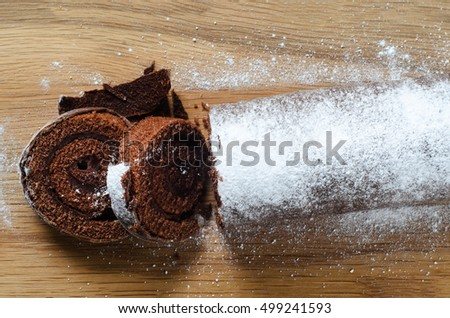 Overhead shot of a chocolate Christmas Yule Log or Swiss Roll cake, sprinkled with icing sugar for snowy appearance on wooden chopping board.