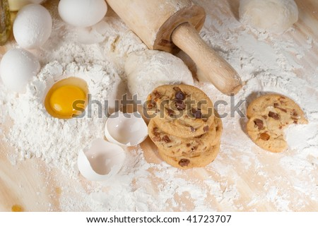 Overhead shot of a few cookies , raw egg and wooden rolling pin - stock photo
