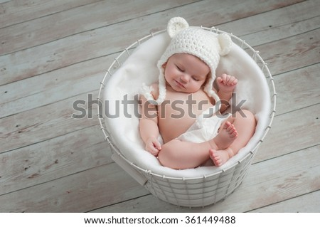 Overhead shot of a four month old baby girl wearing a white, crocheted bear hat. She is sleeping in a wire basket. Shot in the studio on a light wood background. - stock photo