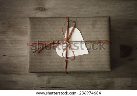 Overhead shot of a gift box with a heart shaped blank label, wrapped in brown paper with a raffia ribbon tied to a bow on wooden planked table.  Vintage appearance with dark tones and  vignette. - stock photo